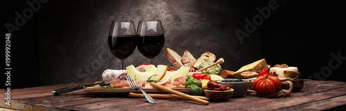 Zestaw przekąsek włoskich antipasti. Odmiana sera, śródziemnomorskie oliwki, ogórki konserwowe, szynka parmeńska z melonem, salami.