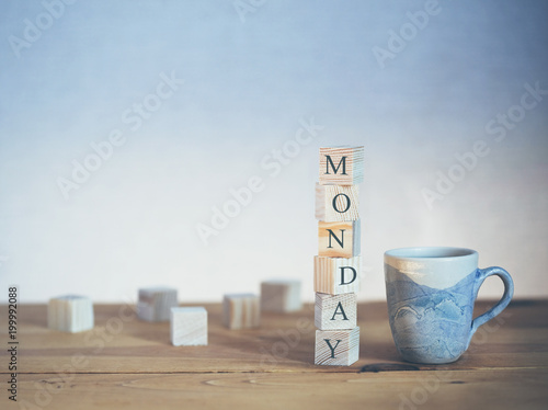 Cup of fresh coffee with Monday word written in wooden blocks