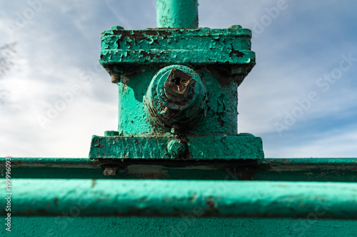 Old green metal structure with peeling paint on the background of sky. Detail of industrial design. - 199996093