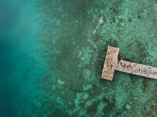 Wooden pier and turquoise water from above