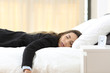 Tired businesswoman on a bed after a bad day - 200002273