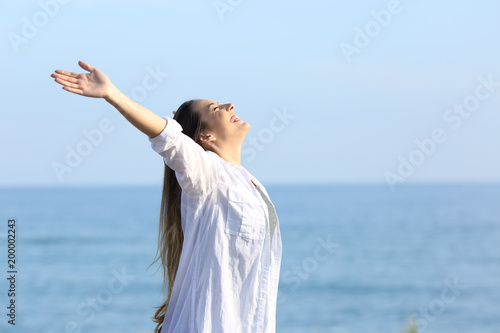 Satisfied woman breathing on the beach
