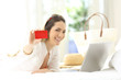 Woman showing a credit card in summer vacations