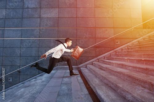 Foto Murales Businessman runs fast over a modern staircase