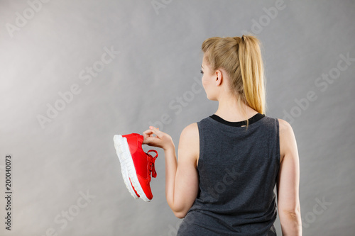 Poster Woman presenting sportswear trainers shoes