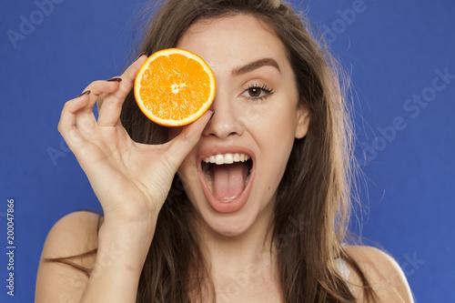 Szczęśliwa młoda kobieta pozuje z plasterkiem pomarańcze na jej twarzy na błękitnym tle
