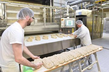 Lebensmittelindustrie: Großbäckerei - Arbeiter backen Brot // Food industry: Bakery - workers baking bread