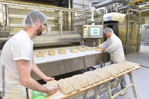 Fototapeta Lebensmittelindustrie: Großbäckerei - Arbeiter backen Brot // Food industry: Bakery - workers baking bread