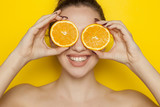 Happy young woman posing with slices of oranges on her face on yellow background