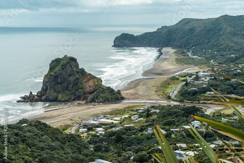 Fotobehang Groen blauw aerial view of town on seashore on cloudy day, Piha beach, New Zealand