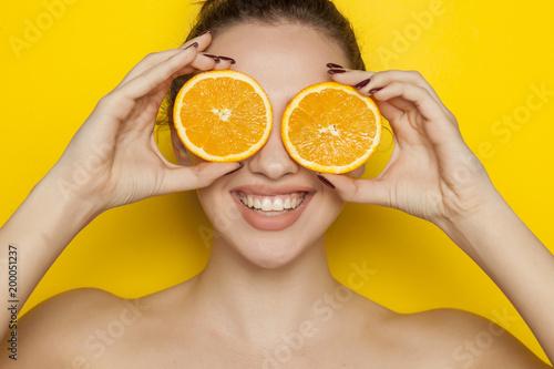 Szczęśliwa młoda kobieta pozuje z plasterkami pomarańcze na jej twarzy na żółtym tle