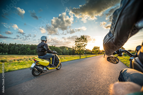 Motor biker riding on empty road with sunset light, concept of speed and touring in nature. - 200059210
