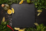 Black slate board with fresh herbs and lemon slices with olive oil