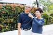 Happy senior Asian couple walking and pointing in outdoor park and house