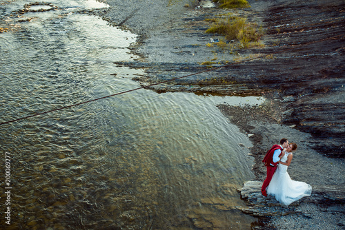 Handsome groom is red suit is kissing his charming bride in the cheeck while standing on the river bank.