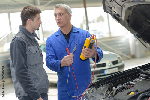 two mechanics looking at and working on a car