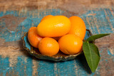 Delicious small citrus fruits kumquats close up on wooden table