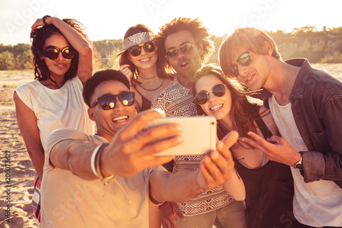 Excited young friends on the beach make selfie
