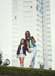 full-height portrait of mother and daughter on the background of a skyscraper. fashionable family look