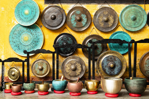 Gongs and singing bowls - traditional Asian musical instruments on a street market. Hoi An, Vietnam. - 200083840