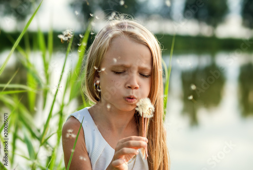girl blowing on dandelion, summer in nature