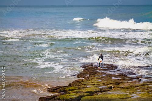 Foto op Plexiglas Marokko A surfer on a rock with a surfboard. Atlantic Ocean