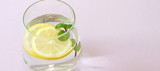Glass of water, lemon and mint. Glass of pure water and fresh organic lemon and mint isolated on purple background. Detox and healthy food concept.