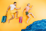 happy young barefoot couple with suitcases running on yellow, summer vacation concept - 200097683