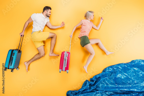 happy young barefoot couple with suitcases running on yellow, summer vacation concept