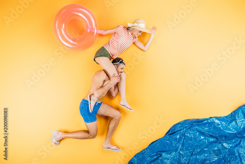 happy young couple with swimming ring having fun together on imagine beach