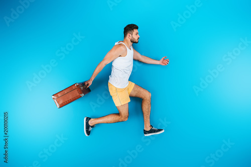 full length view of handsome young man holding suitcase and running on blue