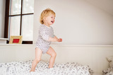 Cute toddler boy jumping on the bed. - 200100444