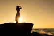 Silhouette of Asian beautiful lady wear white dress is stand posing on rock cliff.