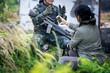 Female journalist interview soldier during war conflict. Photojournalist work on grass field concept.