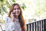 Happy asian girl talking with mobile phone front of high building.
