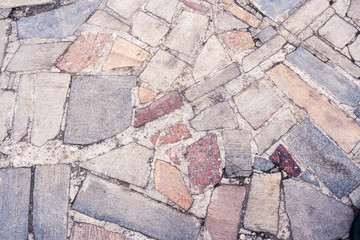 Part of sidewalk consisting of different colored stones as background.