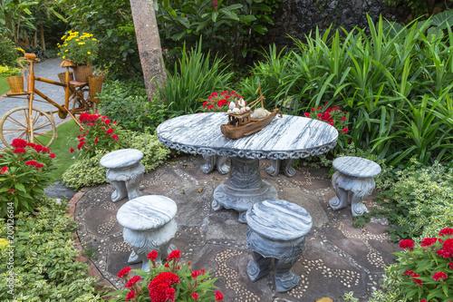 Projektowanie ogrodów. Marmurowy stół z marmurowym taboretem w ogrodzie.