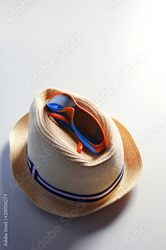 Summer accessories hat and sunglasses on light beige background with copy space for text. - 200136274