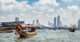 Fototapety Tourist popular boat travel on the Chao Phraya river. To stay in downtown Bangkok. King Rama I Memorial Bridge and skyscrapers of Chinatown is seen on the horizon