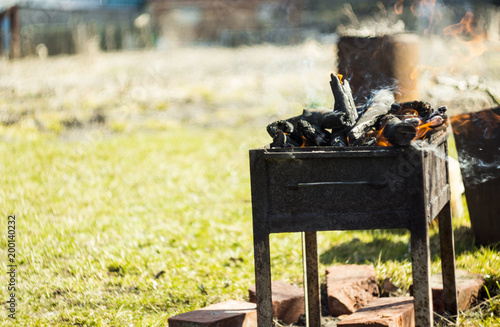 Foto op Aluminium Brandhout textuur brazier with burning fire wood stands on the grass