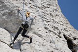 A woman climbing the rocks.
