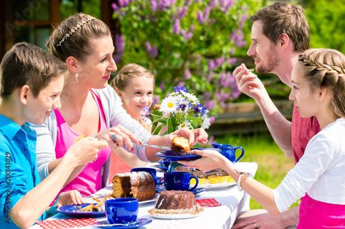 Szczęśliwa rodzina ma kawowego czas w ogrodowym łasowanie torcie