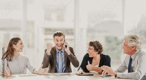 Szczęśliwi ludzie biznesu jest excited przy nową zgodą. Młody biznesmen opowiada na telefonie i pokazuje tak gest. Jego koledzy świętują zwycięstwo. Siedzą przy stole. Koncepcja sukcesu lub pracy zespołowej