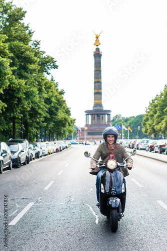 Fotobehang Berlijn Tourist in Berlin riding scooter in dense traffic
