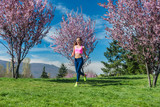 Woman doing sport running on hill between cherry trees blossoming