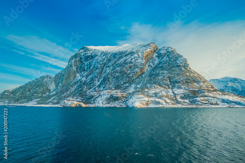 Foto Murales Outdoor view of coastal scenes of huge mountains partial covered with snow durig a trip in Hurtigruten in a blue sky