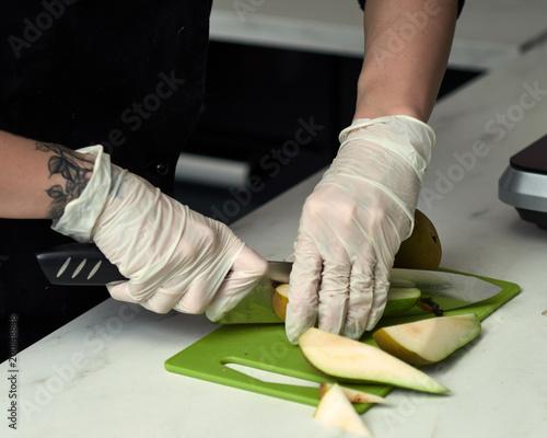 Krok-po-kroku przygotowanie czarnego projektanta ciasta. Cukiernik ścina gruszkę.