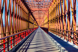 Red iron bridge crossing a river with roadway. © solipa