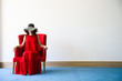 Beautiful young woman in red dress and red chair, in white room with blue floor