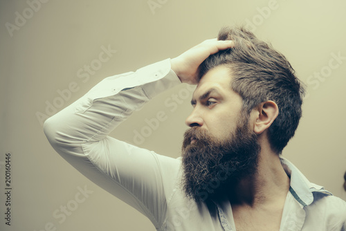 Barbershop or hairdresser concept. Macho on strict face, wears unbuttoned shirt. Man with long beard, mustache and stylish hair, light background. Guy with modern hairstyle visited hairdresser.